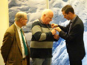 Raoul van Ketel brengt de erespeld aan bij Folkert-Jan Geertsma, die evenals Arthur Schuering 50 jaar lid is.